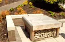 Sitting walls to Cedar table with cobble filled galvanized baskets